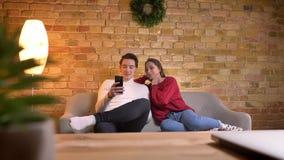 年轻白种人夫妇坐评论的沙发观看入智能手机和meltingly在家庭环境的内容 影视素材