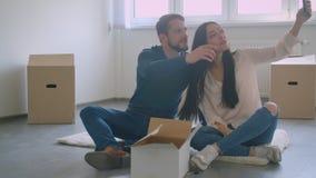 年轻白种人夫妇坐选择被构筑的照片的新房地板地方 股票视频