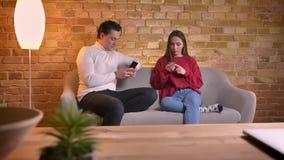年轻白种人夫妇画象坐有智能手机的沙发和谈话互相在家庭环境 影视素材