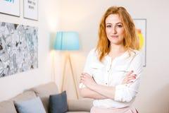年轻白种人女孩身分在办公室和在明亮交叉她的横跨她的胸口迷人的少女的双臂工作里面 免版税库存照片