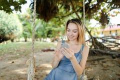 年轻白种人女孩骑马摇摆和使用smatrphone、沙子和树在背景中 免版税图库摄影