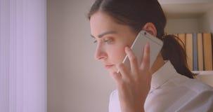 年轻白种人女实业家特写镜头画象有看通过窗口身分的电话在办公室 影视素材