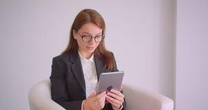 年轻白种人女实业家特写镜头画象玻璃的有在坐的片剂的一视频通话在扶手椅子 影视素材