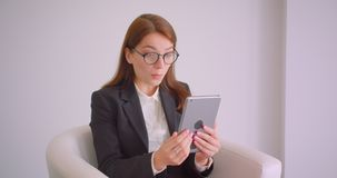 年轻白种人女实业家特写镜头画象玻璃的有在片剂挥动的喂坐的一视频通话在 影视素材