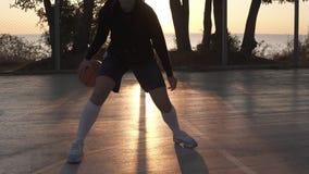 年轻白种人女性在法院的蓝球运动员滴下的和实践的控制球技巧 早晨黄昏,太阳发光 影视素材