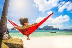 年轻白种人女性放松在热带b的一个红色吊床 库存照片