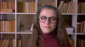 年轻白种人女生特写镜头画象挥动她的顶头说法的玻璃的没有看照相机在学院 股票录像