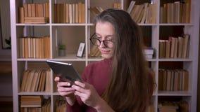 年轻白种人女生特写镜头画象玻璃的使用户内片剂在户内大学图书馆里 股票录像