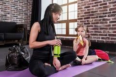 年轻白种人妇女和一个愉快的放松在瑜伽训练以后的女孩孩子坐有腿的席子横渡了喝 库存照片