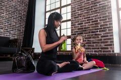 年轻白种人妇女和一个愉快的放松在瑜伽训练以后的女孩孩子坐有腿的席子横渡了喝 免版税库存图片