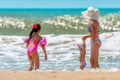 年轻白种人妇女和两个小女儿看以后的波浪获得乐趣由在晴朗的黑海海滩的水在风暴 库存照片