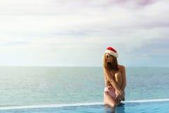 年轻白种人妇女在放松由游泳池的圣诞老人帽子 免版税图库摄影