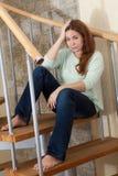 年轻白种人妇女坐木螺旋形楼梯在她自己的家 免版税图库摄影