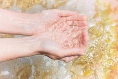 年轻白种人妇女女孩用杯形手挖出在岩石和海草背景的透明海水 明亮的阳光 免版税库存照片