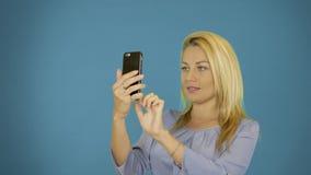年轻白种人妇女拍在智能手机的照片 坚实蓝色背景 女性画象腰部 白肤金发俏丽微笑 影视素材