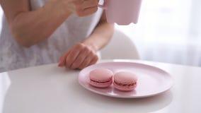 年轻白种人妇女饮用的茶用在白色厨房的桃红色蛋白杏仁饼干 股票视频