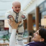 年轻白种人妈妈使用与她逗人喜爱的快活的男婴, throing他并且在公共场所再捉住 库存照片