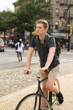 年轻白种人少年骑马自行车画象在城市街道上的 免版税库存图片