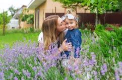 年轻白种人户外母亲亲吻小女儿 家庭休息在村庄 图库摄影