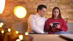 年轻白种人朋友特写镜头画象坐殷勤地coworking与在家庭环境的片剂的沙发 股票录像