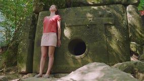 年轻白种人白肤金发的女孩在与一个古老都尔门的梦想站立 股票录像