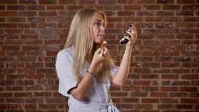 年轻白种人白肤金发的女孩在背景中做自己构成,搽粉他的面颊,砖墙 股票视频
