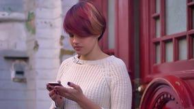年轻白种人粉发的女孩画象快乐与在红色门背景的智能手机一起使用 股票录像
