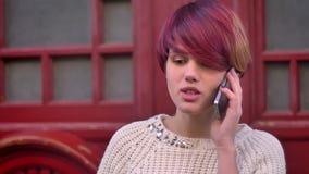 年轻白种人粉发的女孩画象快乐谈话在红色门背景的智能手机 股票录像