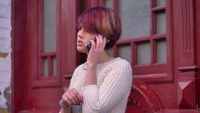 年轻白种人粉发的女孩画象殷勤地谈话在红色门背景的手机 影视素材