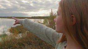 年轻白种人金发碧眼的女人指向在秋天湖岸的一个手指  影视素材