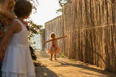 年轻白肤金发儿童女孩使用室外与她的朋友或姐妹和妈咪 温暖的日落光 家庭夏天trave 免版税库存图片