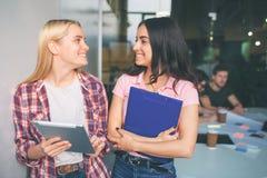 年轻白肤金发和深色的模型的图片一起站立和微笑 他们看起来愉快 年轻女人对负电子和 免版税库存图片