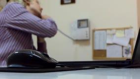 年轻白肤金发的人在个人计算机在家工作 他移动他的老鼠并且叫某处 股票视频