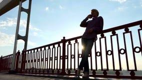 年轻白肤金发的人在Slo Mo享受在一座河桥梁的精采日落有机动性的 股票视频
