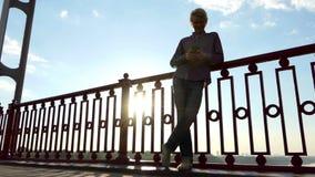 年轻白肤金发的人在Slo Mo享受在一座河桥梁的精采日落 影视素材