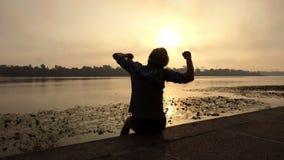 年轻白肤金发的人坐并且举他的在河岸的拳头在日落在Slo Mo 影视素材