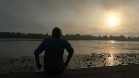 年轻白肤金发的人并且跳坐河岸在慢动作的日落 股票录像