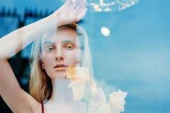 年轻白肤金发的可爱的妇女的画象有虹膜的在玻璃后开花 图库摄影