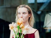 年轻白肤金发的可爱的妇女的画象有虹膜的在玻璃后开花 库存图片