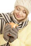 年轻白肤金发的喝热的饮料的妇女佩带的冬天成套装备 库存图片