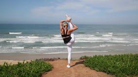 年轻白肤金发的在海洋附近的女子实践的瑜伽姿势 股票视频
