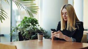 年轻白肤金发的女孩与智能手机sittig一起使用在咖啡馆的桌上 股票录像