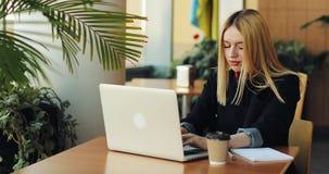 年轻白肤金发的女孩与膝上型计算机sittig一起使用在咖啡馆的桌上 自由职业者寻找一个工作,打印某事 影视素材