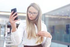 年轻白肤金发的女实业家在商业中心的采取selfie 免版税图库摄影