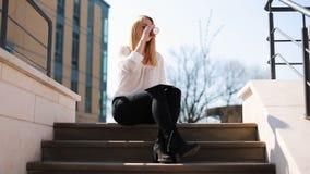 年轻白肤金发的妇女与片剂一起使用坐外部的台阶和饮用的咖啡 影视素材