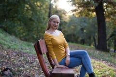 年轻白肤金发的妇女坐一条长凳在森林里,享受自然 免版税图库摄影