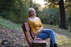 年轻白肤金发的妇女坐一条长凳在森林里,享受自然 免版税库存照片