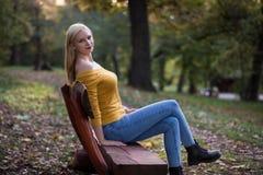 年轻白肤金发的妇女坐一条长凳在森林里,享受自然 库存图片
