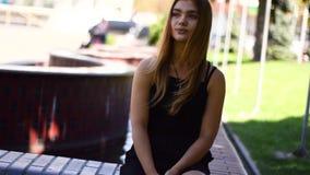 年轻白肤金发的妇女坐与喷泉的一条长凳在背景 股票视频