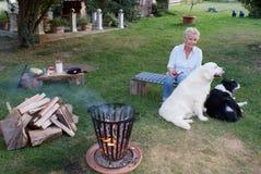年轻白肤金发的妇女坐与她的金毛猎犬和博德牧羊犬由营火 免版税图库摄影